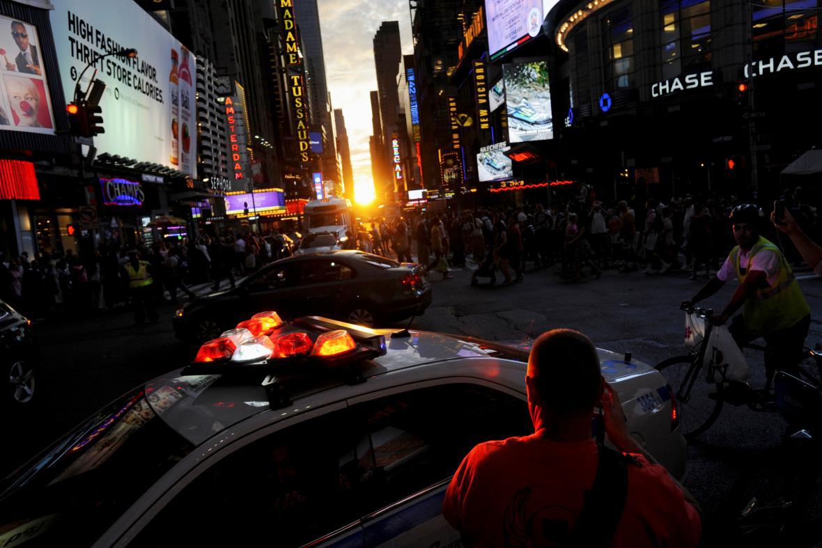 Lidé pozorují zapadající Slunce nad Manhattanem