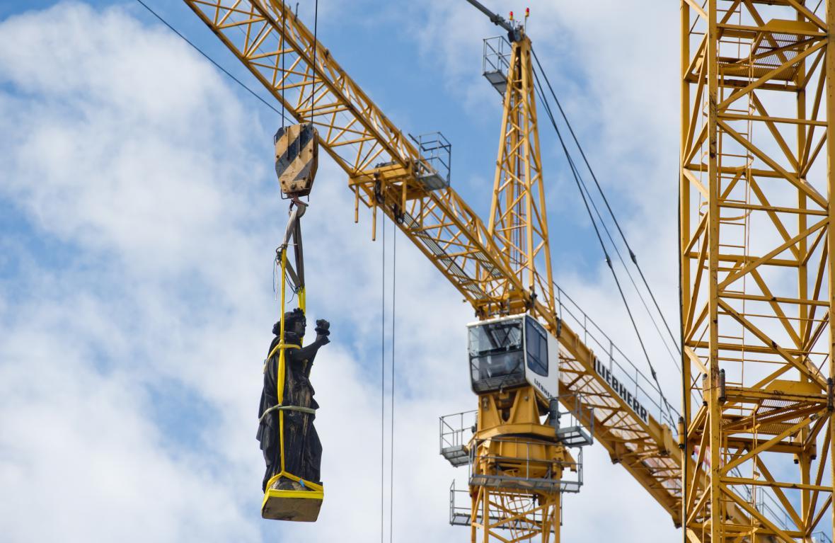 Jeřáb stěhuje sochu Ohně z balustrády Národního muzea