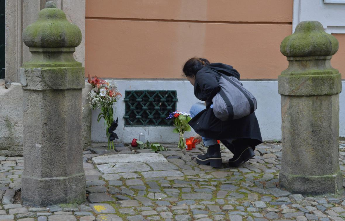 Lidé nosí květiny před francouzskou ambasádu v Praze