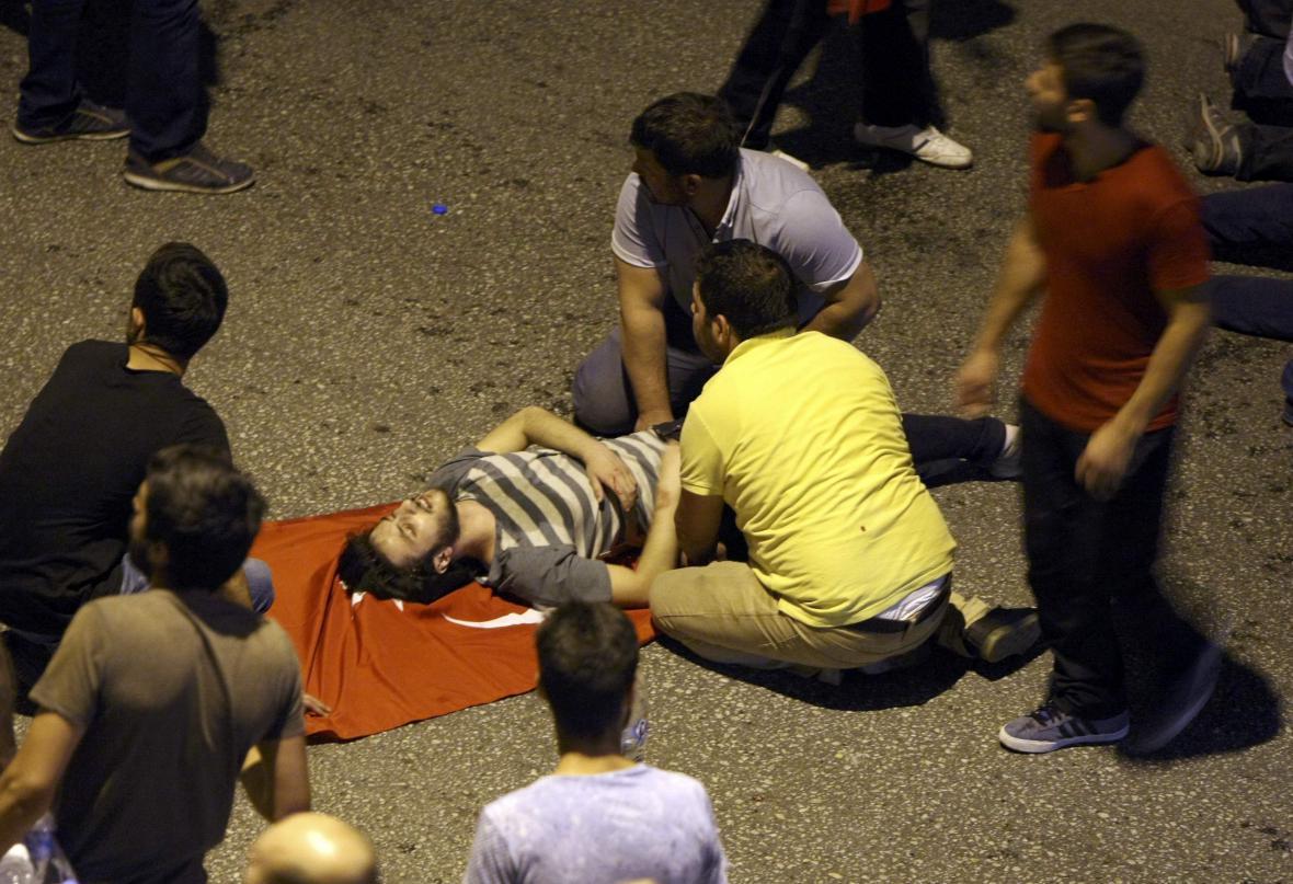 Lidé v ulicích Ankary ošetřují zraněného muže