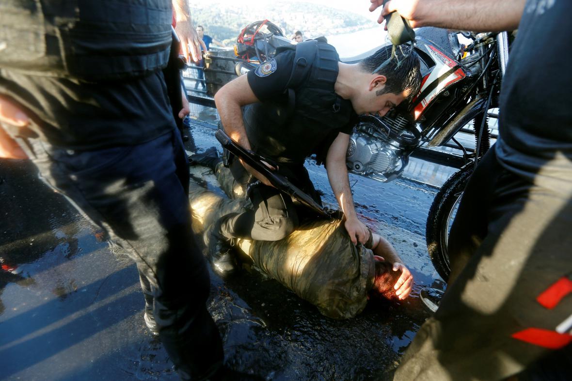Policista kontroluje jednoho z vojáků, kterého zlynčoval dav Erdoganových stoupenců