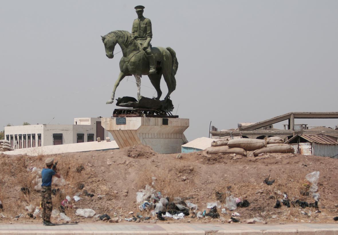 Kurdský bojovník střílí na sochu bratra syrského prezidenta Asada ve městě Hasaká