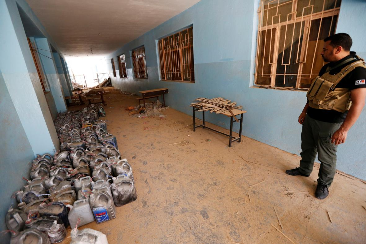 Člen iráckých bezpečnostních složek stojí u výbušnin, které zůstaly ve škole ve Fallúdži po islamistech