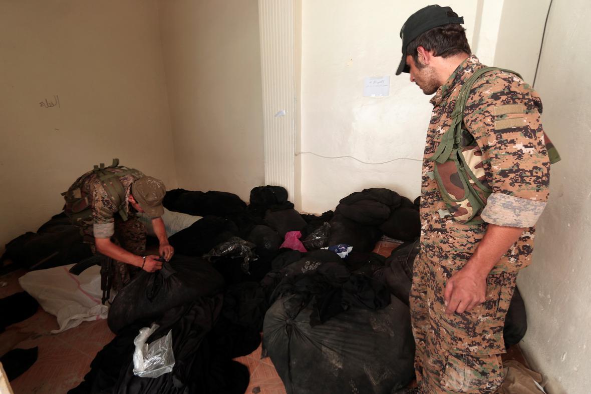 Syrské demokratické síly (SDF) prohlížejí pytle s nikáby v místnosti, kde působila náboženská policie IS (Manbidž)