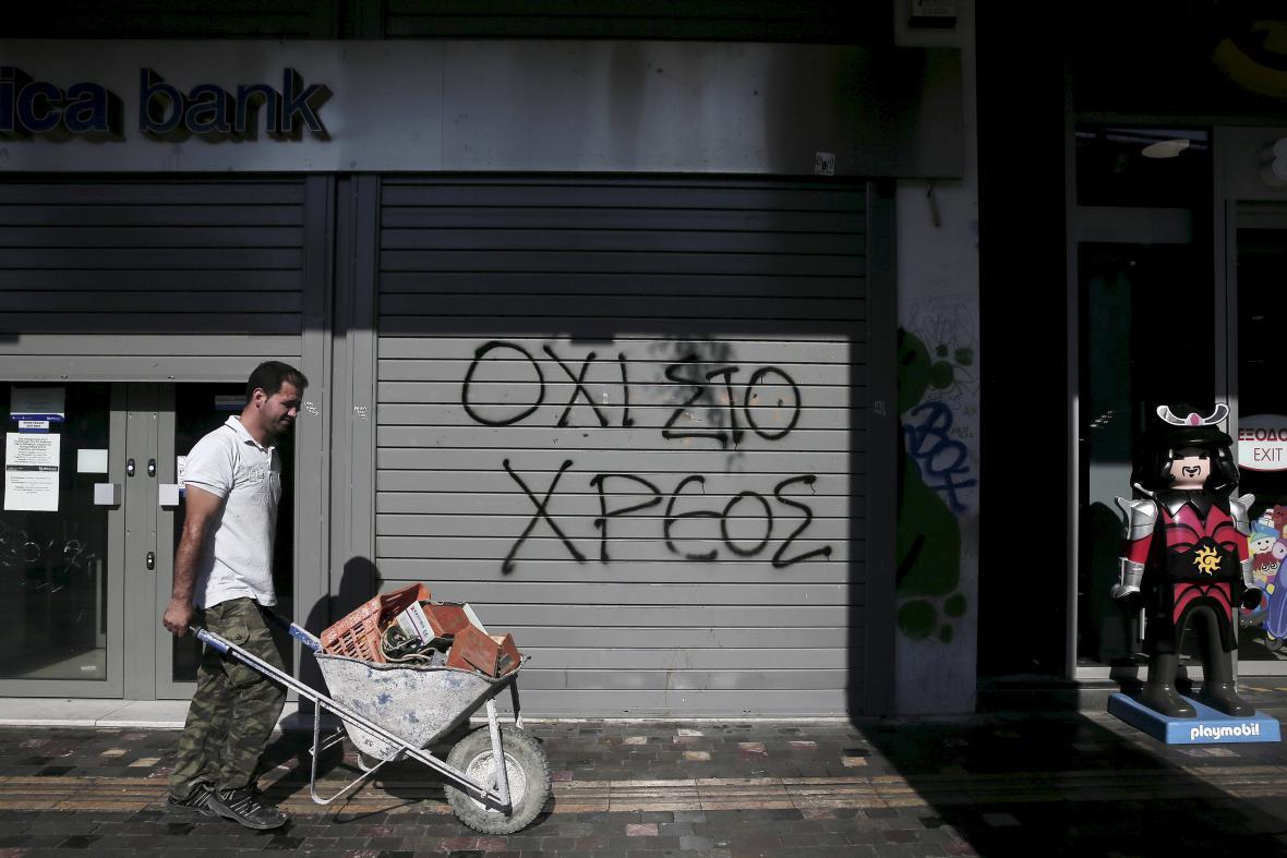 Muž veze kolečko aténskými ulicemi, v pozadí banka s graffiti: