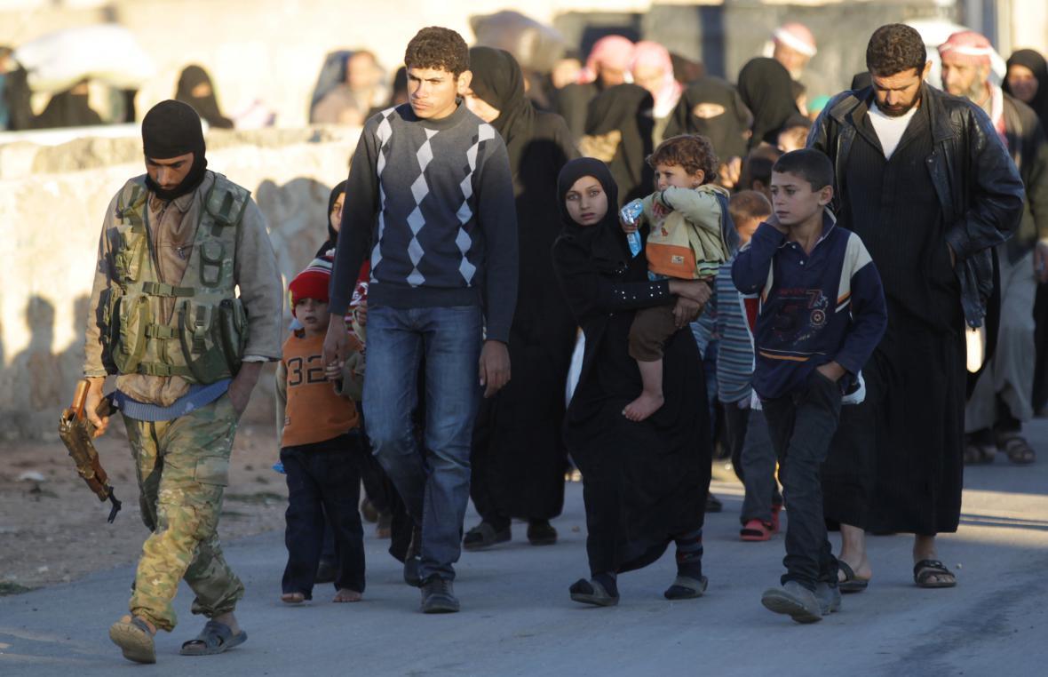 Jeden z rebelů odvádí lidi, kteří uprchli před IS
