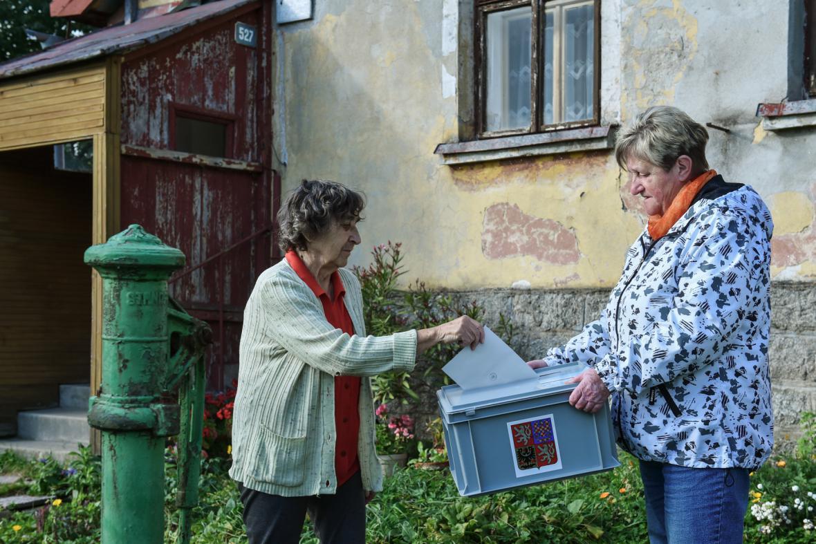 Jedna z voliček v Kořenově na Jablonecku odevzdává hlas do přenosné urny
