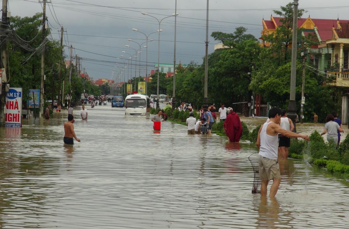 Lidé v zatopených ulicích chytají ryby