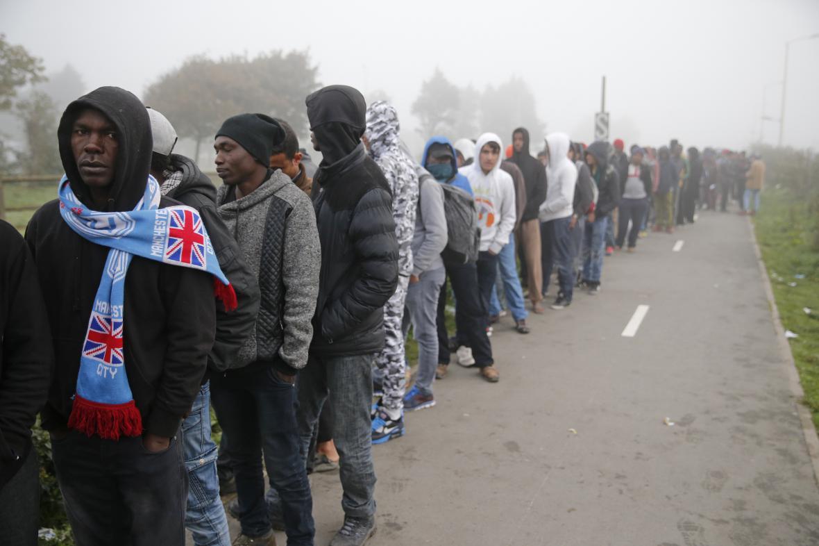 Skupina běženců čeká na přesun do jiných částí Francie