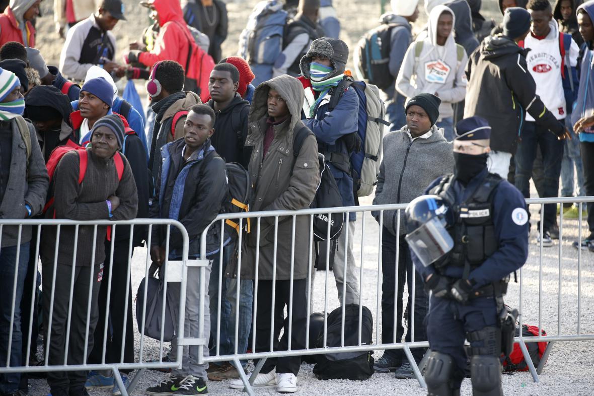 Nezletilí migranti v bývalém táboře u Calais čekají na autobus