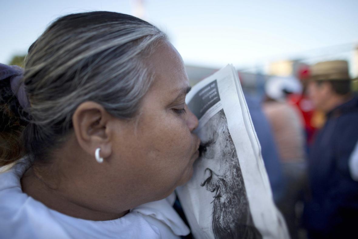 Kubánská žena líbí portrét s Fidelem
