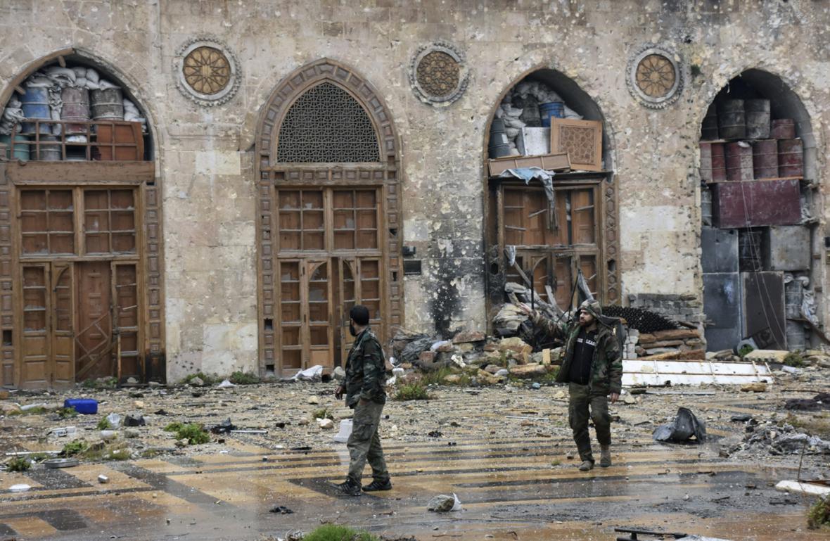 Provládní vojáci procházejí zničenou mešitou v Aleppu