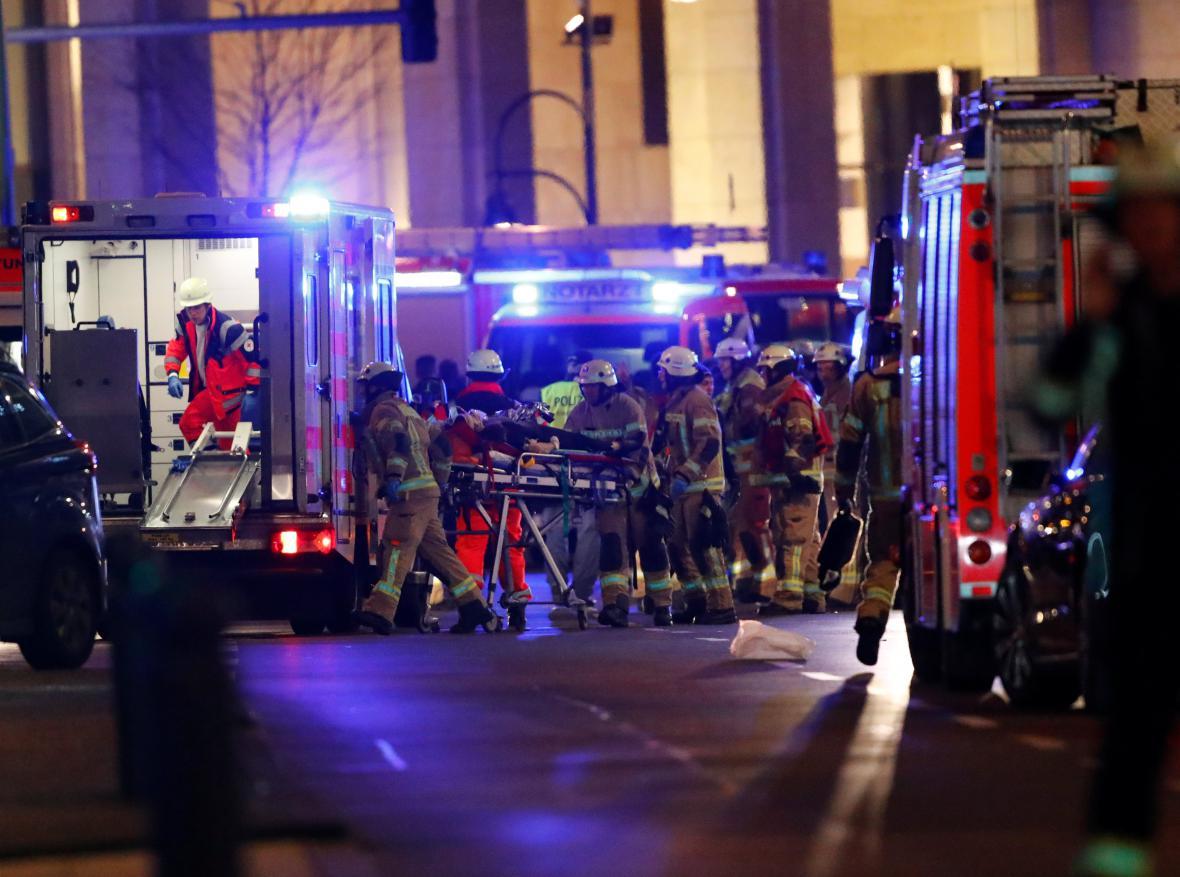 Záchranáři odvážejí zraněné z berlínského vánočního trhu
