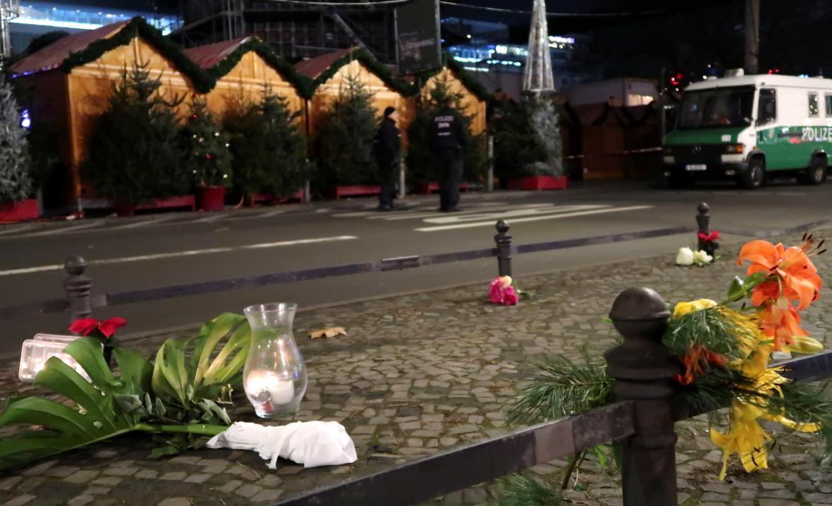 Lidé nosí k místu činu květiny a svíčky