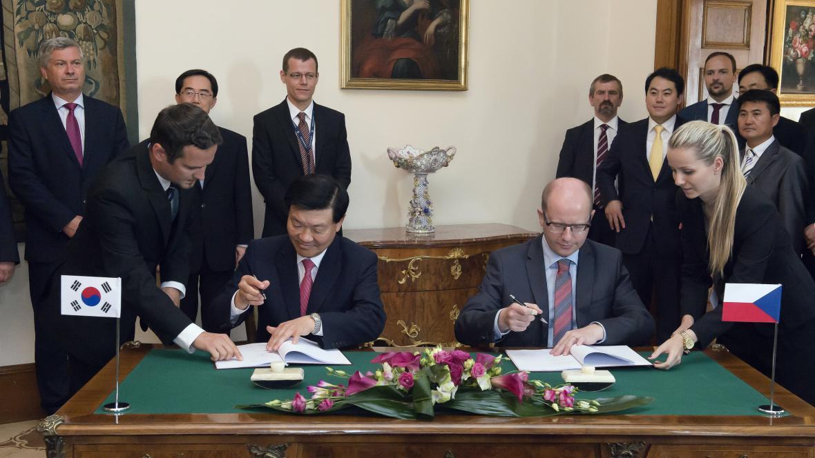 Premiér Bohuslav Sobotka a prezident korejské firmy Hyundai Mobis Čong Mjong-čchul podepisují investiční smlouvu, na základě které poskytlo Česko firmě investiční pobídky přes 400 milionů korun