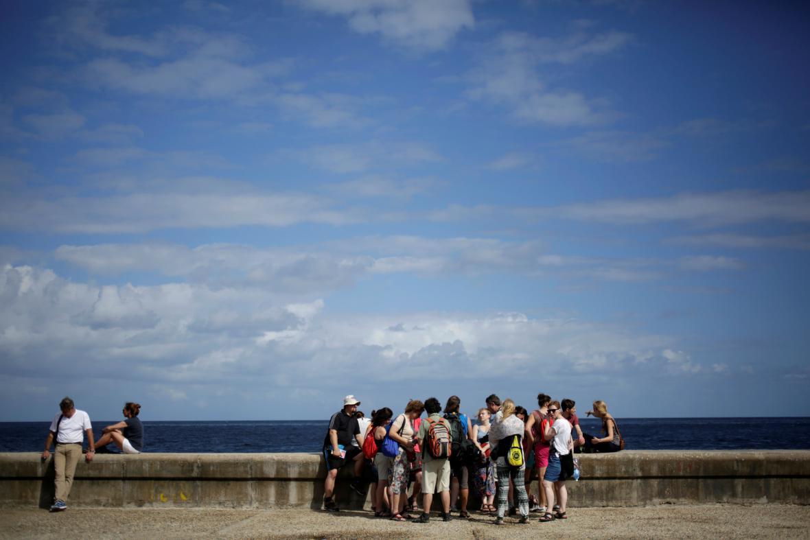 Turisté na hlavním pobřežním bulváru Malecon v Havaně