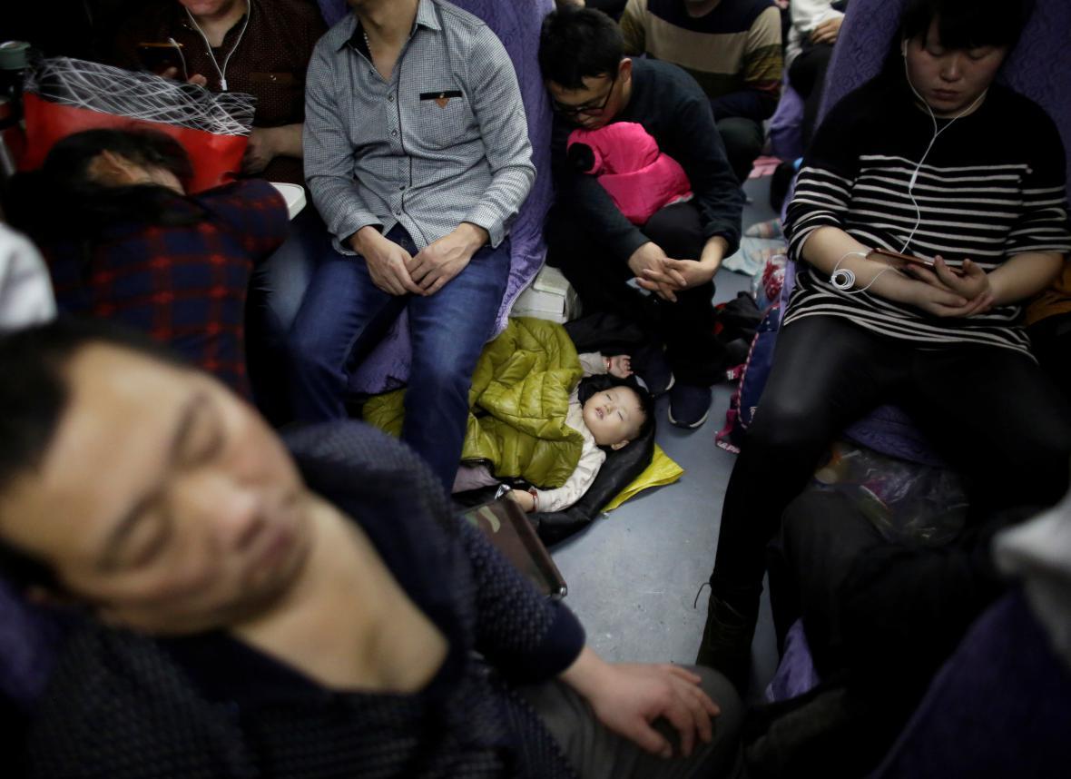 Dítě spící na podlaze vlaku směřujícího do Šanghaje před nadcházející oslavou čínského nového roku
