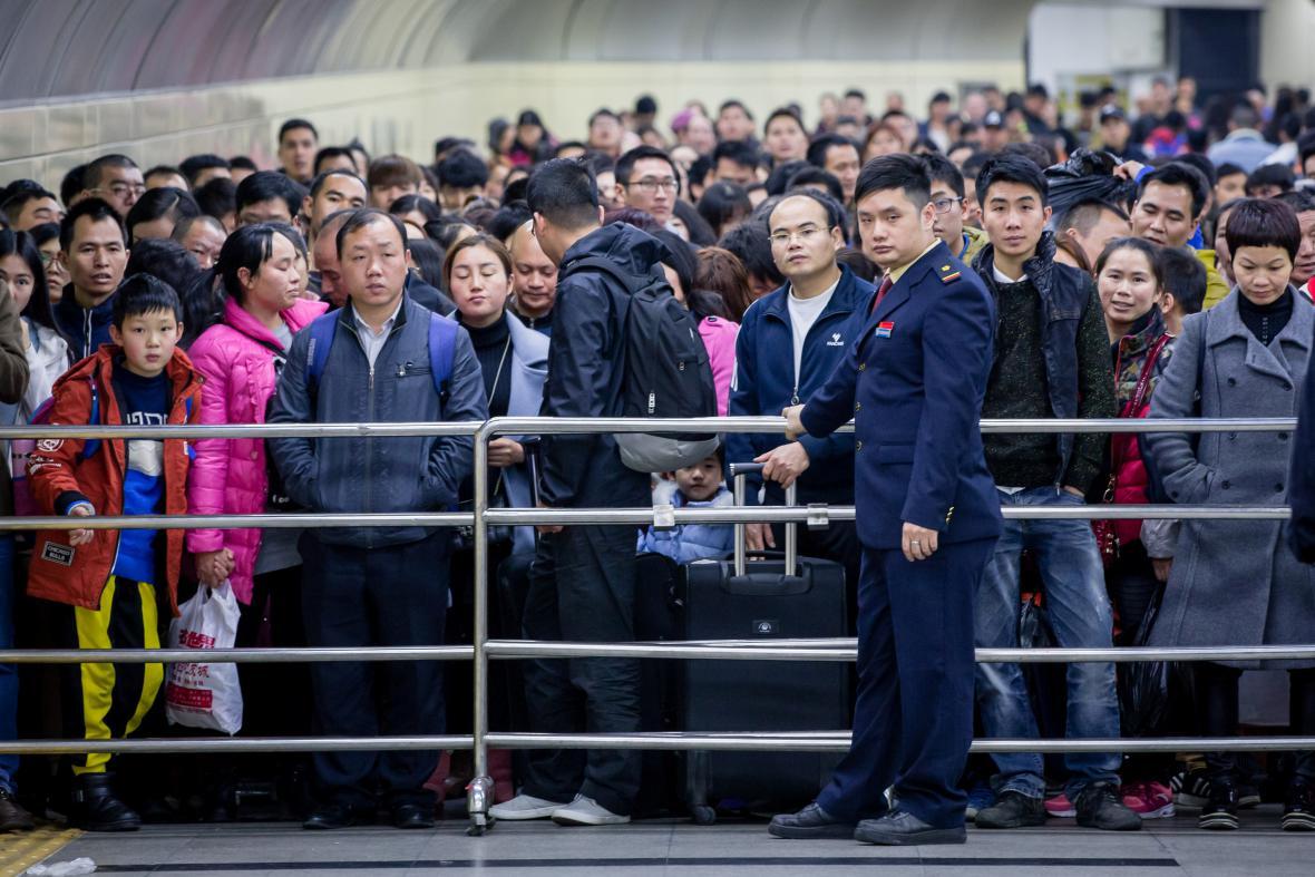 Lidé čekají na vpuštění na železniční stanici v jihočínském městě Kanton