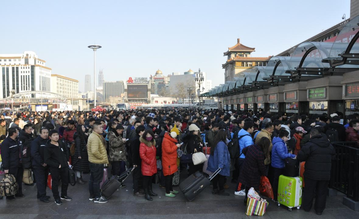 Lidé v Pekingu se chtějí dostat na vlak, aby se na oslavy příchodu nového roku dostali domů