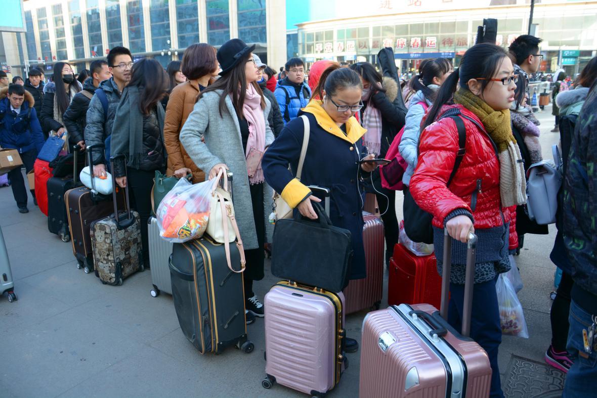 Cestující čekají v dlouhé frontě, aby se dostali na nádraží ve městě Ťi-nan