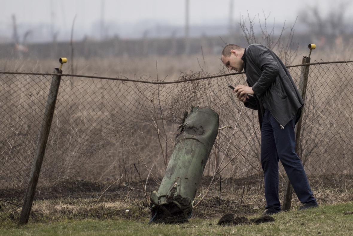 Muž fotografuje zbytek munice v blízkosti místa požáru