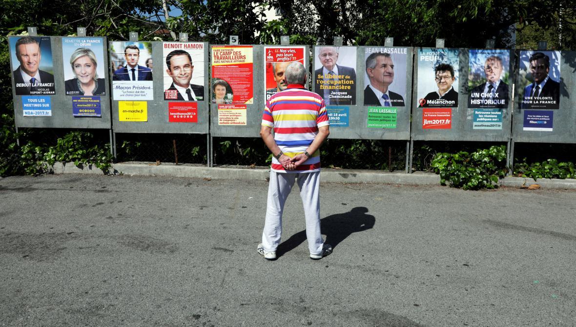 Muž se upřeně dívá na plakáty jednotlivých prezidentských kandidátů
