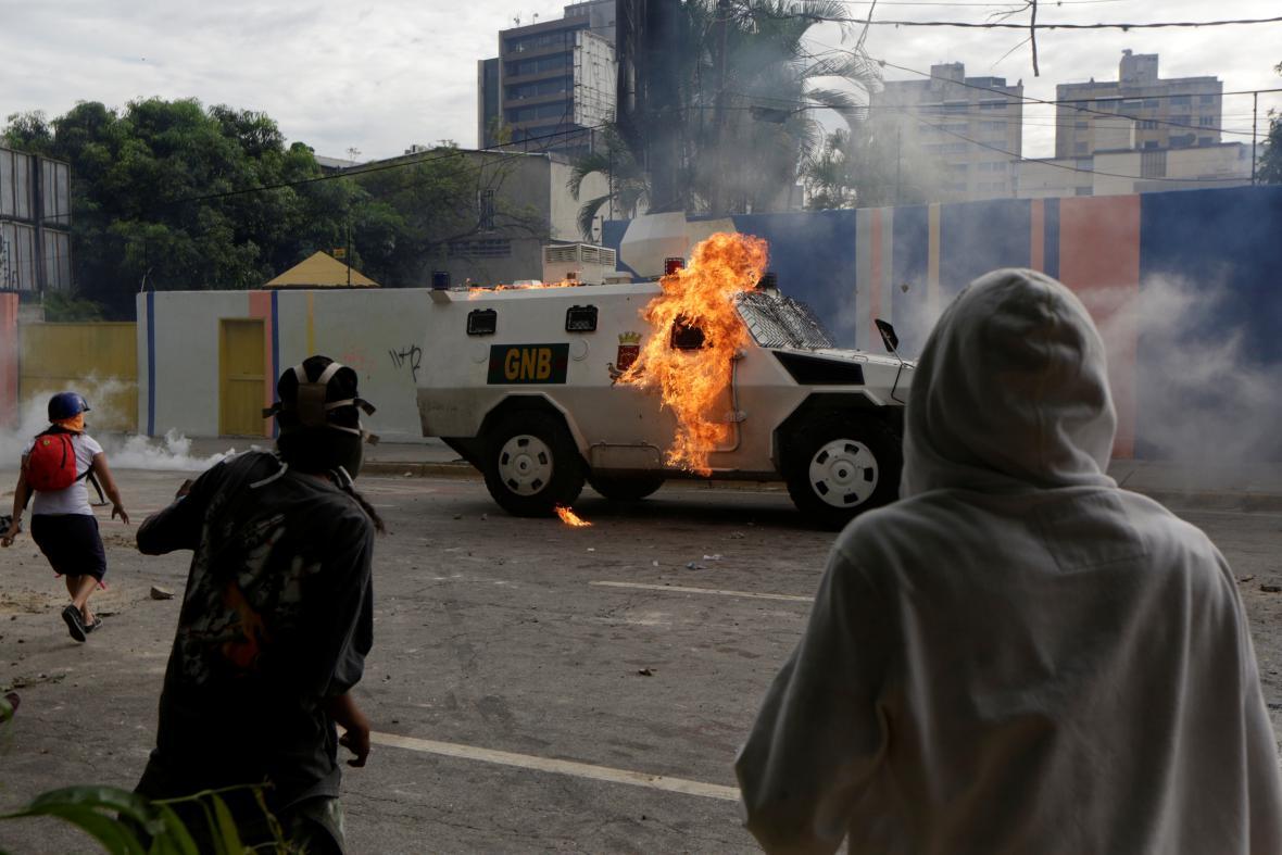 Stoupenci opozice při protestech zapálili obrněné auto policie