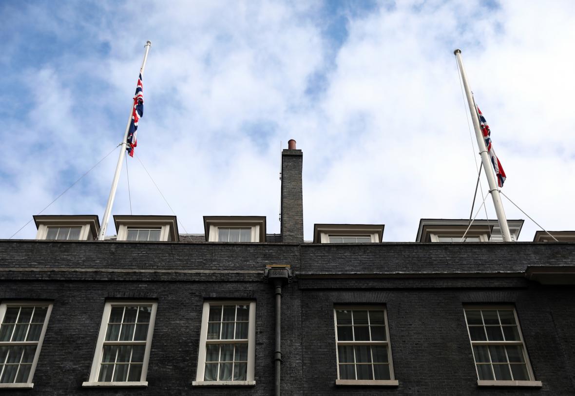 Vlajky na půl žerdi na budově, kde sídlí britská premiérka