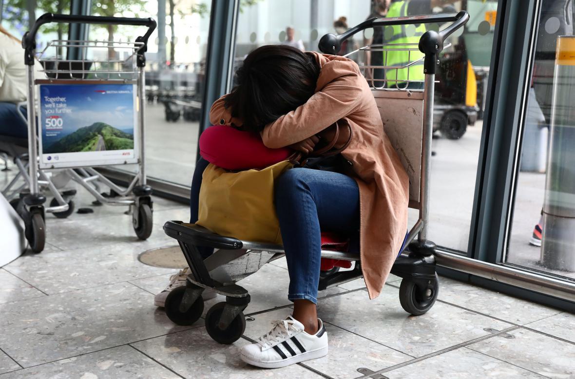 Spící cestující na letišti Heathrow