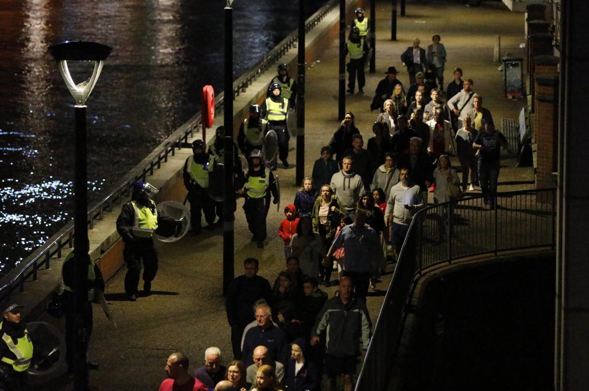 Policie odvádí lidi do bezpečí