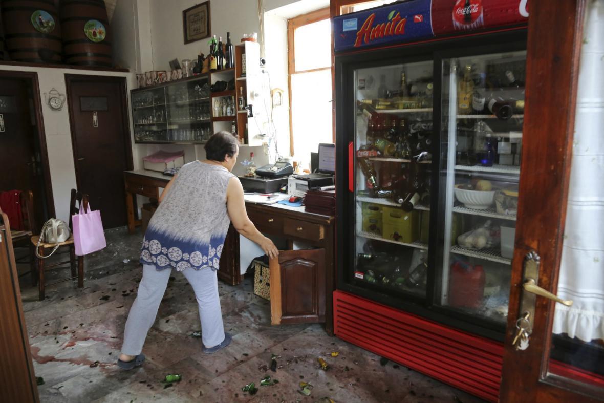 Žena uklízí svůj obchůdek po zemětřesení v Plomari