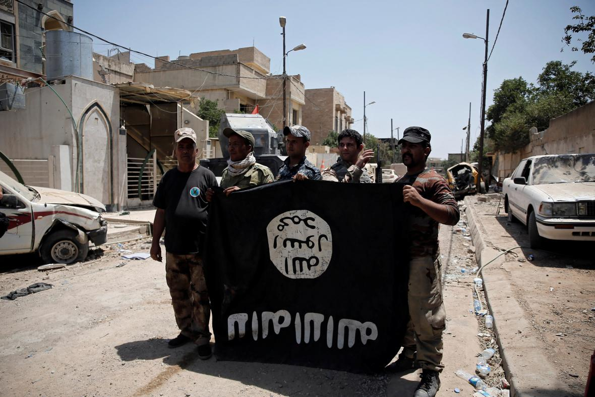 Iráčtí vojáci s ukořistěnou vlajkou islamistů