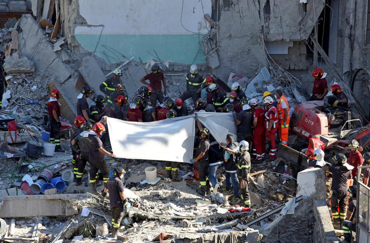 Záchranáři vyprošťují z trosek zříceného domu těla obětí