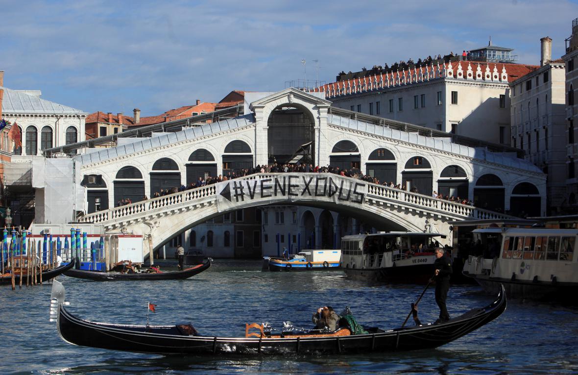 """Obyvatelé volající po omezení turismu vyvěsili na most Rialto transparent, který hlásá """"Venice exodus"""""""
