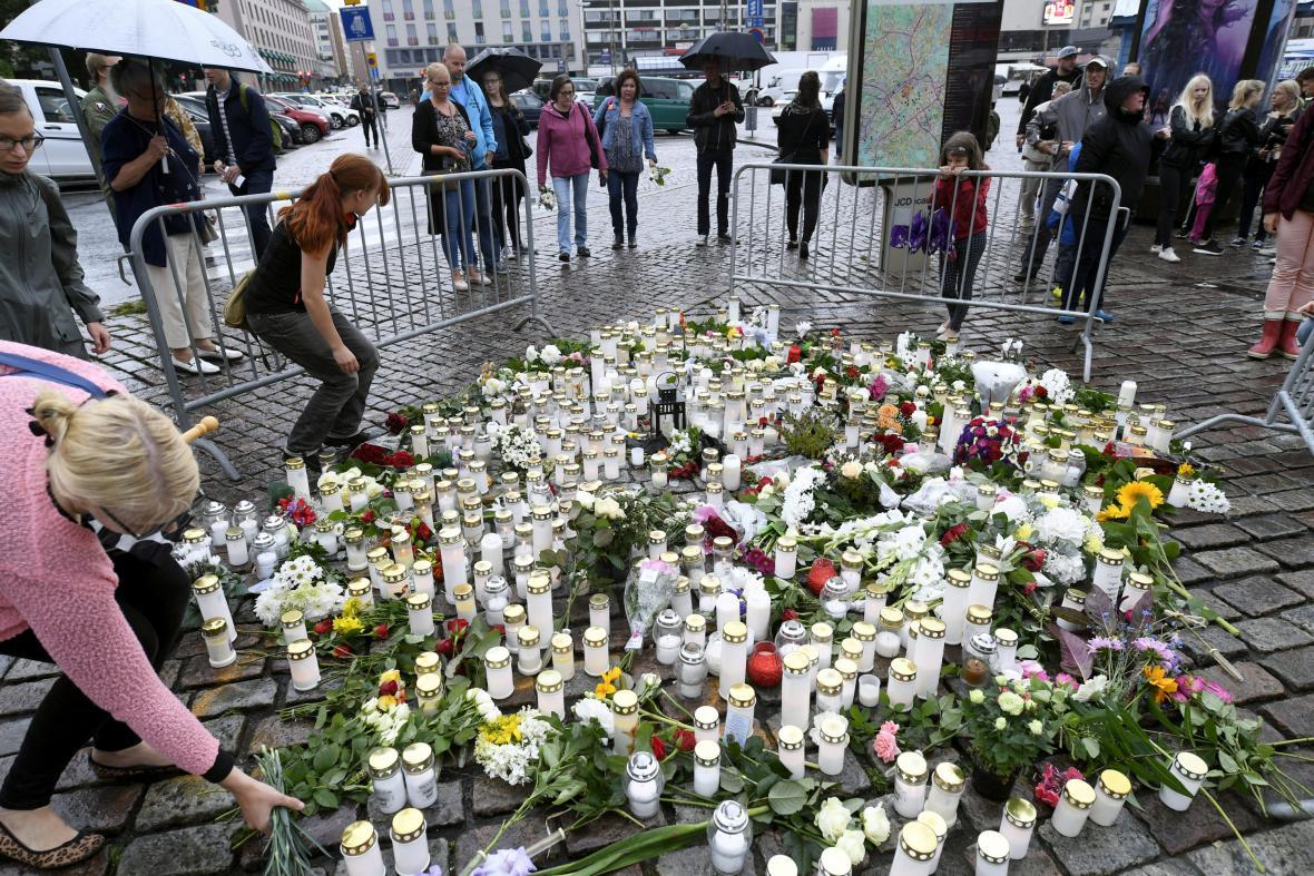 Lidé zapalují svíčky na náměstí v Turku, kde útočník zabil dva lidi
