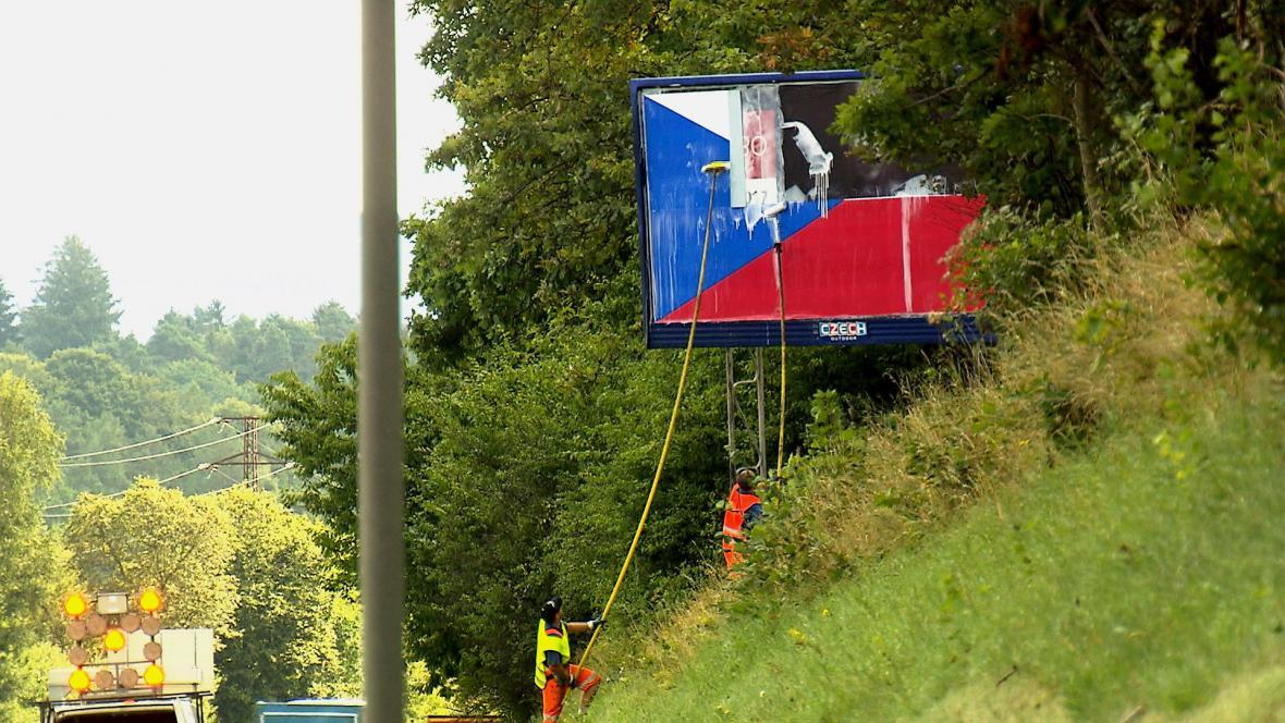 Pracovníci vylepují vlajku na billboard