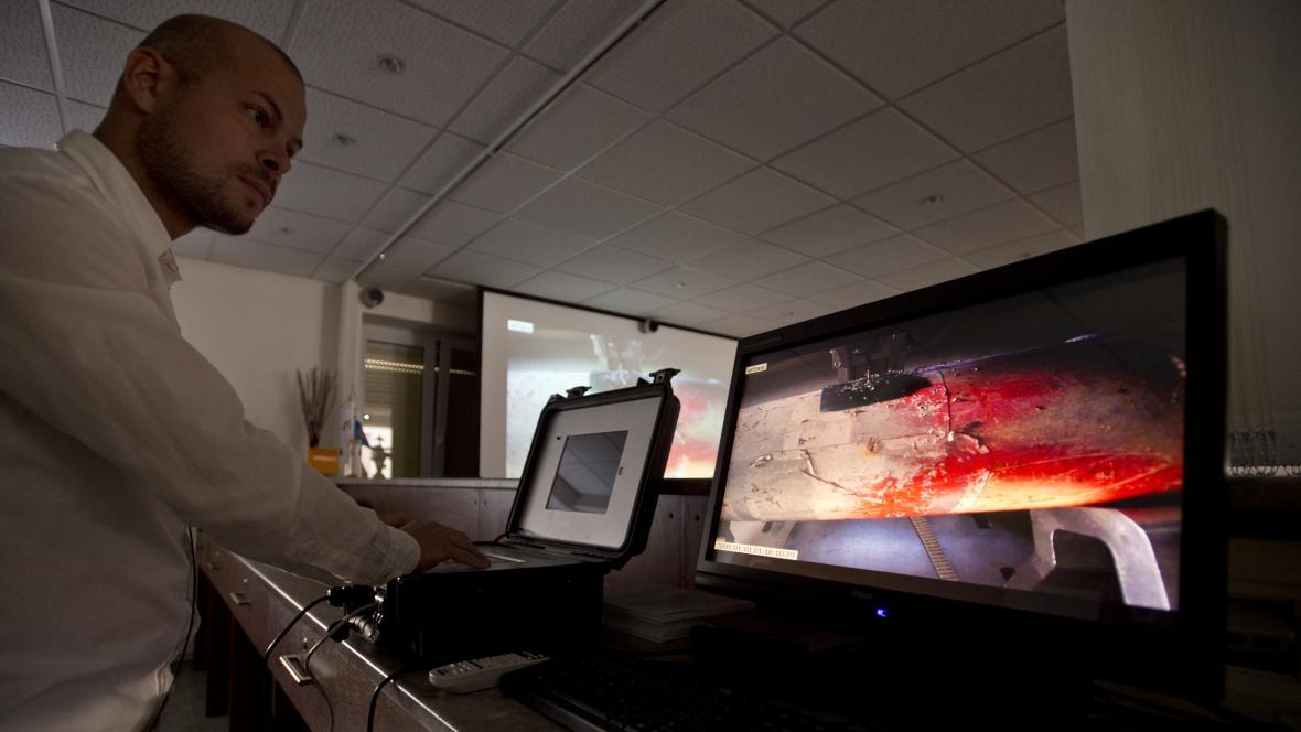 Pracovníci ústavu na monitoru na dálku sledují kontrolu neznámého vzorku umístěného v tlakové lahvi