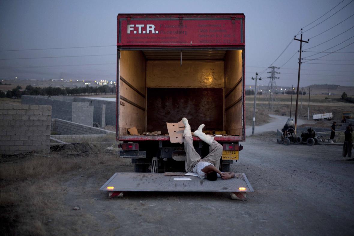 Ali Arkady / Vyčerpaný dělník usíná na nakládací rampě dodávky (8. 6. 2011, Sulajmánija, Irák)
