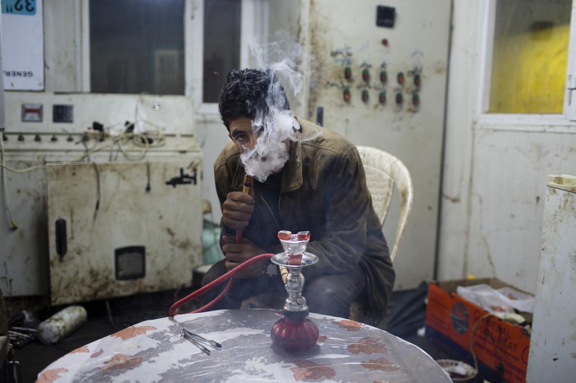 Sebastian Meyer / Vysídlený jezíd ze Sindžáru, kouří tabák s vonnou příměsí z malé vodní dýmky v provizorní boud (19. 2. 2015, Tandžero, Irák Džamal)