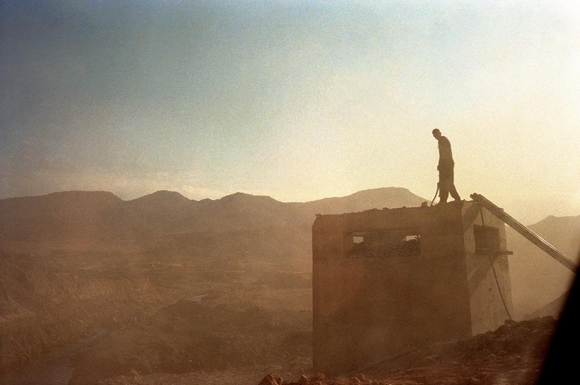 Stefano Carini / Muž pracující na střeše budovy vedle silnice mezi městy Erbíl a Sulajmáníja (Květen 2014 – Hory u města Koya, Irák)