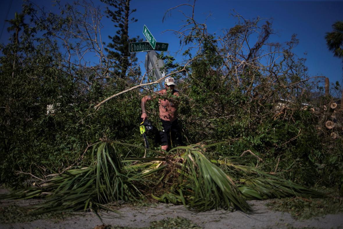 dobrovolník odklízí polámané palmy na floridském Chokoloskee Island