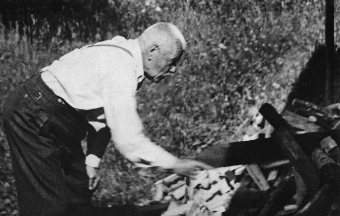 Petr Bezruč při řezání dříví; foceno tajně z terasy Bezručova srubu na Ostravici