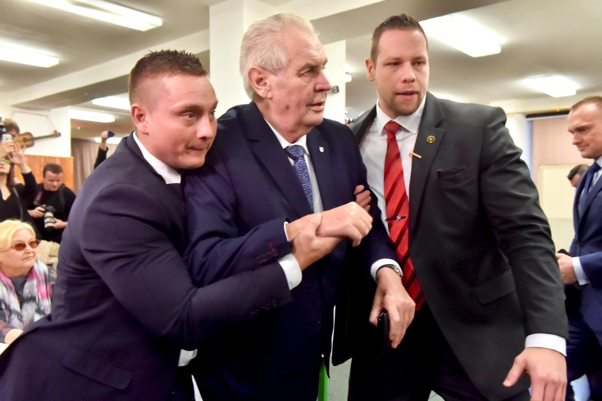 Ochranka odvádí Miloše Zemana z volební místnosti