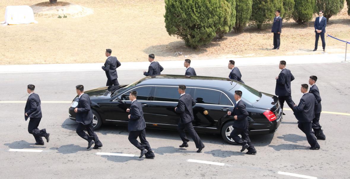 Osobní strážci Kim Čong-una doprovází jeho limuzínu cestou na oběd