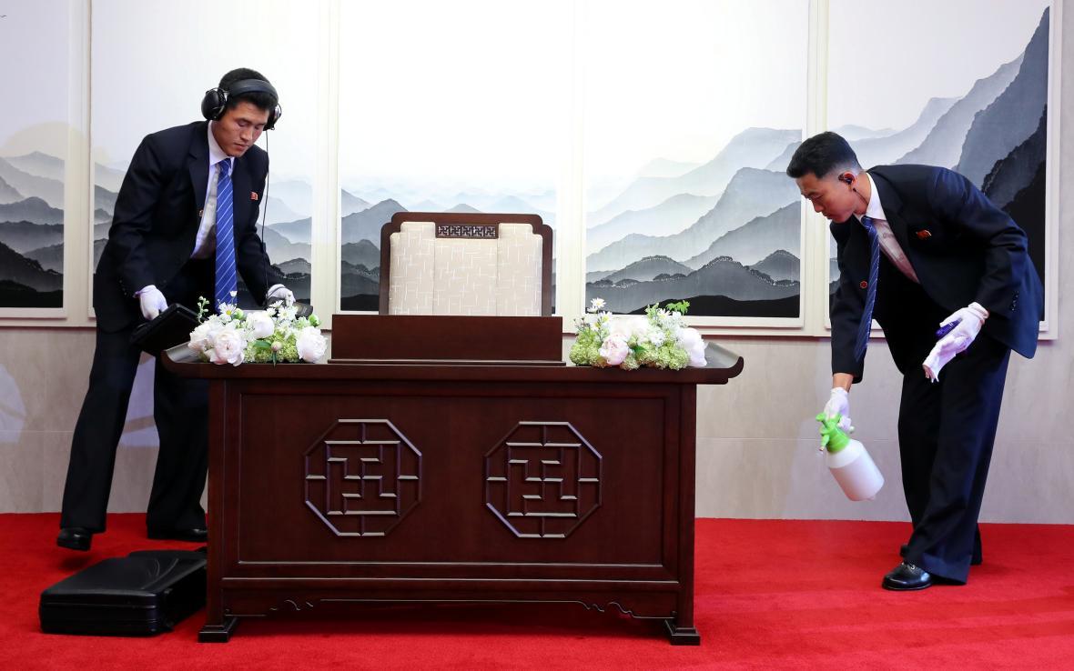 Severokorejský bezpečnostní tým dezinfikuje místo, kde se posléze Kim Čong-un podepsal do knihy hostů