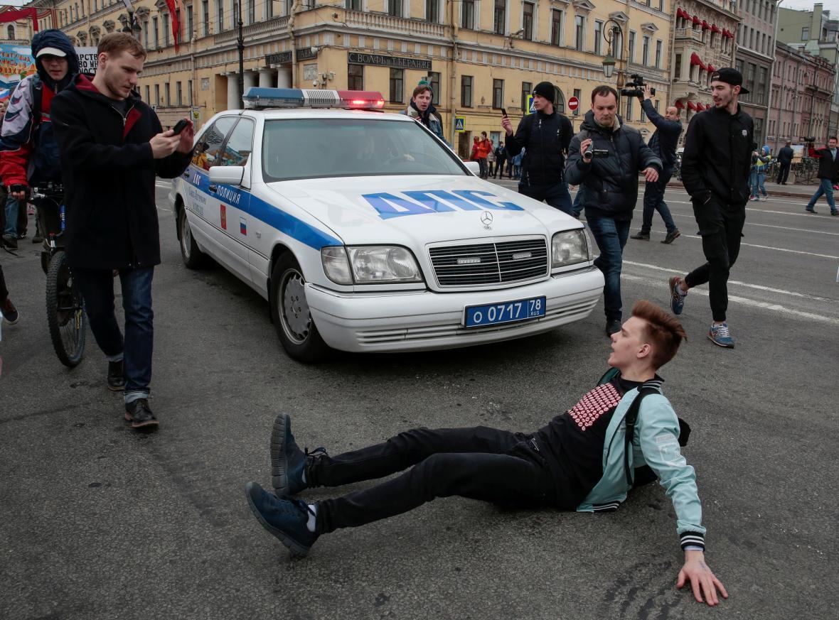 Demonstrant v Petrohradě blokuje policejní auto
