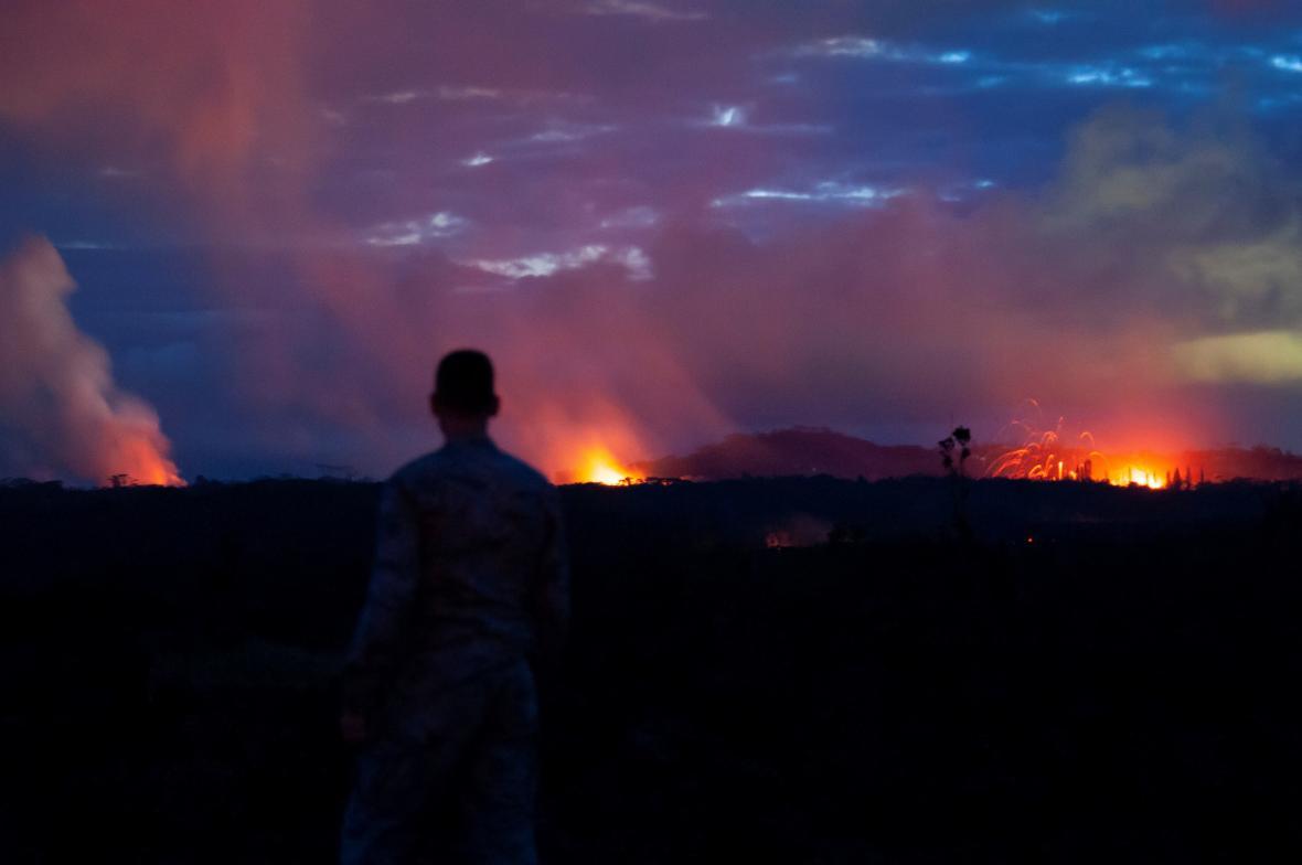 Voják sleduje trhliny, z nichž uniká láva