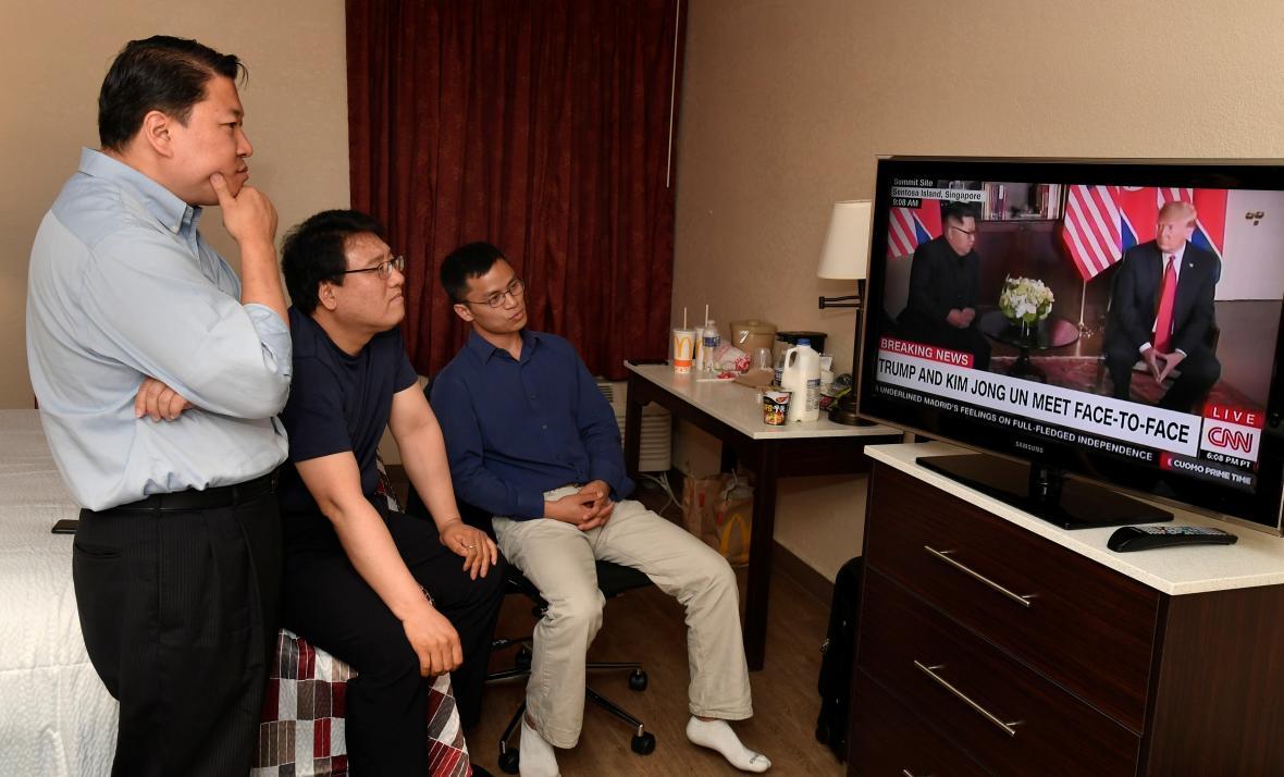 Severokorejský přeběhlík Justin Kim (vpravo) sleduje dění v Singapuru