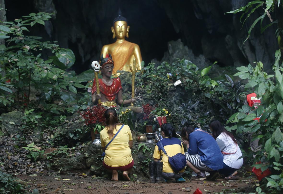 Členové rodiny se modlí před buddhistickou sochou v blízkosti jeskyně