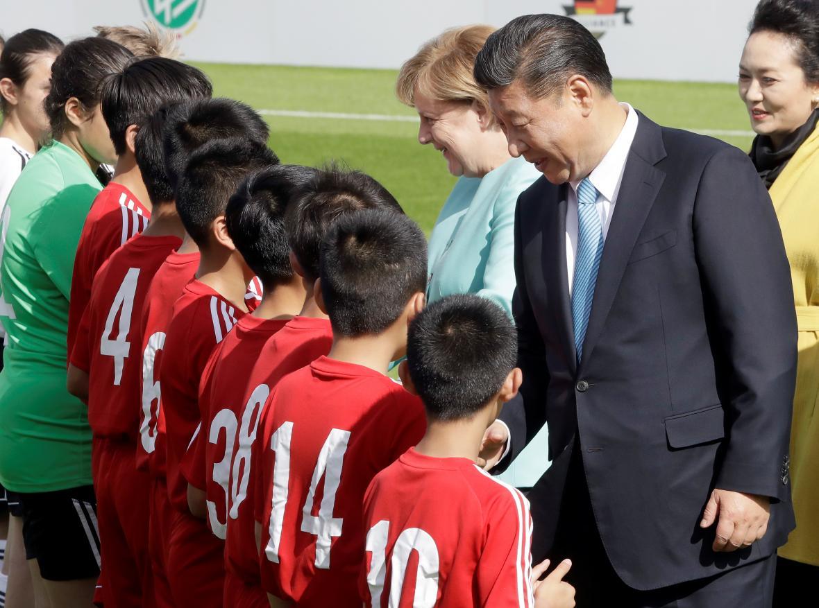 Čínský prezident s německou kancléřkou mezi malými fotbalisty